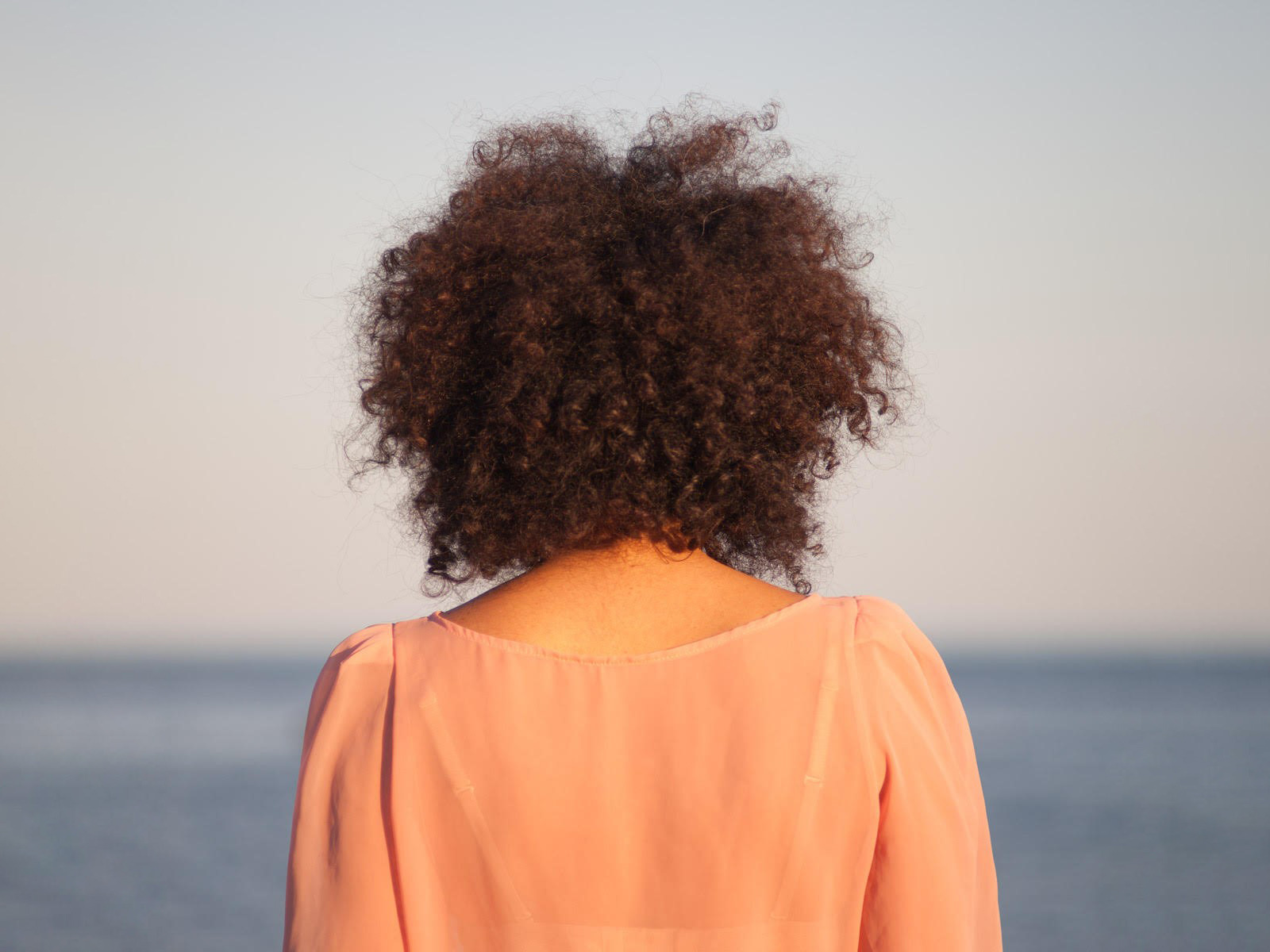 Cloudless image - back of woman staring off into the distance.